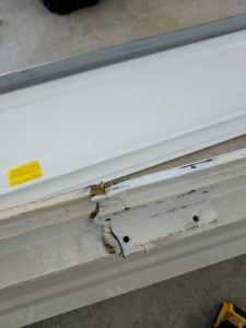 cracked garage door panel as a result of bad garage door opener installation